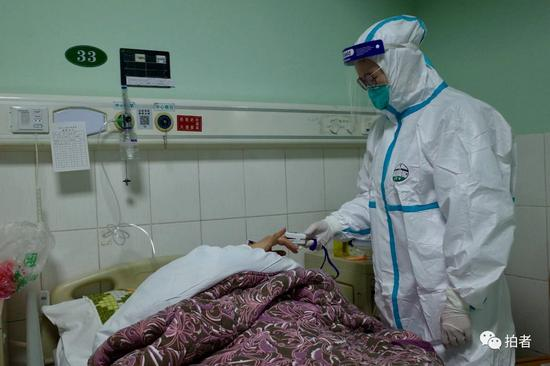 △1月22日,中南医院隔离区一病房内,医务人员为一新型冠状病毒患者测量体温。
