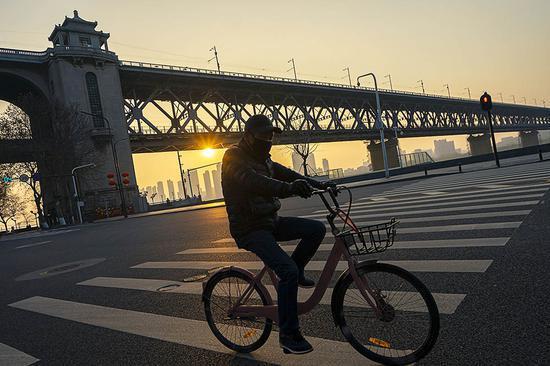 2月4日,一名市民在武汉长江大桥附近骑车。 新华社  图