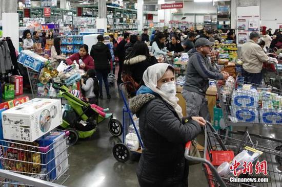 当地时间3月13日,位于美国纽约皇后区的一家大型超市,民众排队购买物资。中新社记者 廖攀 摄