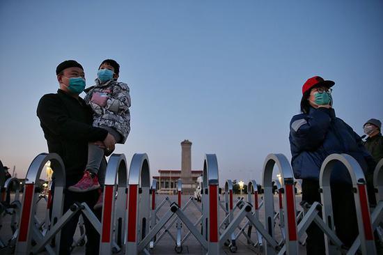市民戴着口罩观看升旗仪式。