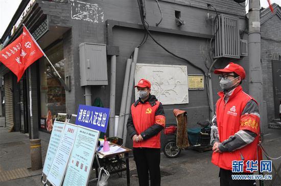 2月27日,自愿者张开国(左)和儿子张洪赫在北京市东城区清闲门街道花圃社区车辇店胡同口的疫情防控值班点值守。 新华社记者 鞠焕宗 摄