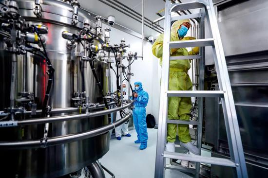 4月10日,工作人员在国药集团中国生物新冠疫苗生产基地尚未投产的新型冠状病毒灭活疫苗生产车间内调试、清洁设备。图/新华