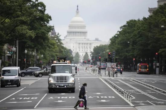 ▲9月9日,一名男子在美国华盛顿国会大厦附近过马路。(新华社)