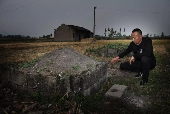 2018年5月1日,四川省绵竹市兴隆镇广平村,吴加芳在亡妻的坟前,向妻子默念说话,他经常如此。新京报记者 尹亚飞 摄
