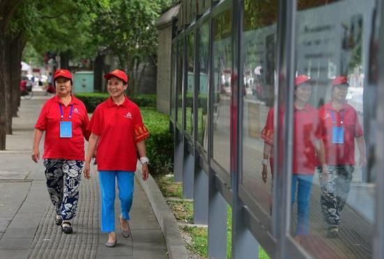 """2015年7月12日,北京,""""西城大妈""""孟大妈(左)和丁大妈准备去居委会所在的胡同巡逻。视觉中国 资料图"""