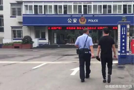 ▲周某被警方带走。