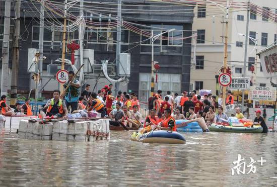谷饶镇华里社区,救援队准备进入积水区送物资。