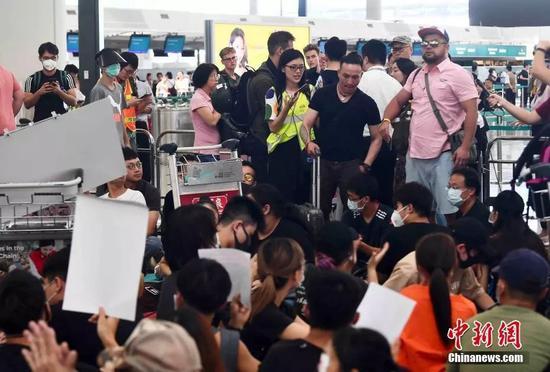 8月13日下午,大批示威者以机场手推车等堵塞香港国际机场1号客运大楼旅客登机行段及保安闸门,旅客未能经1号客运大楼前往离境大堂。中新社记者麦尚旻 摄