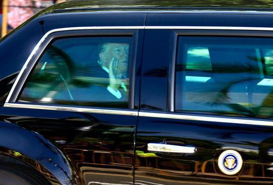 美国总统特朗普在自己的专车内向外招手。此次新加坡之行,是他首次到访,除了会见李显龙和金正恩,他没有户外参访活动。