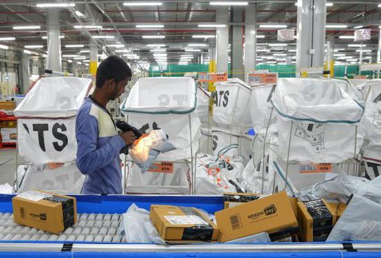 資料圖片:印度當地人在亞馬遜印度公司旗下物流子公司ATS工作。(法新社)