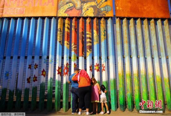 资料图:当地时间2016年11月6日,墨西哥提华纳,移民家庭隔着美墨边境之间的隔离墙聊天。