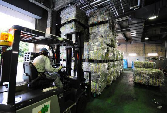 在日本東京都港區資源垃圾處理中心,工作人員運送初步處理好的塑料瓶。(資料圖片)