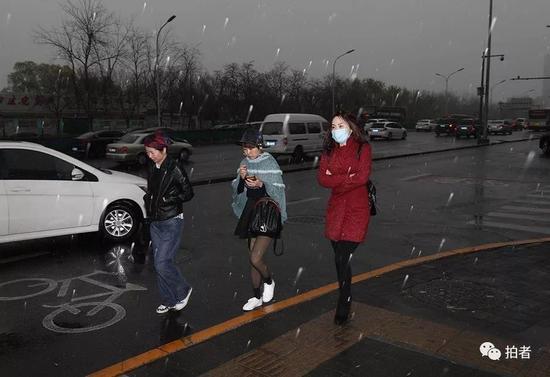 △ 4月4日下午,西三环,雪中的市民。摄影/新京报记者浦峰