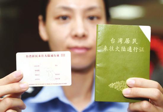 图为北京市公安局出入境管理总队的一名民警在展示电子台胞证样证(左)和本式台胞证的对比。新华社记者陈晔华 摄