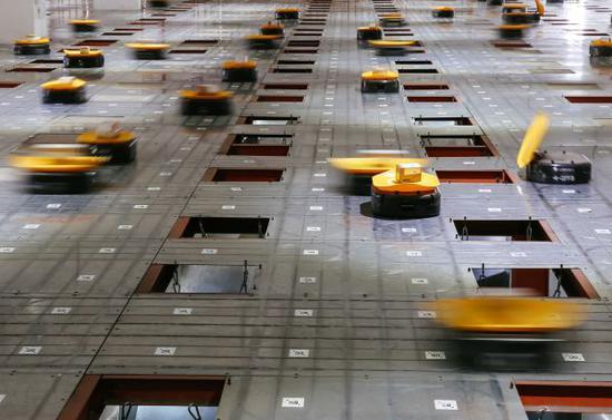 资料图片:在义乌申通公司,机器人运载包裹进行分拣(2017年5月3日摄)。新华社记者 张铖 摄
