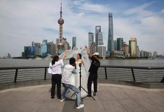 6月2日,上海外滩。新娘正以浦东新区陆家嘴的楼宇群为背景拍摄婚纱照。新京报记者 尹亚飞翻拍