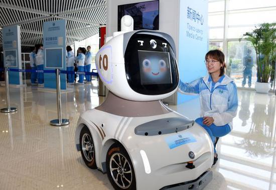 """上合组织青岛峰会志愿者展示新闻中心机器人""""海海""""(李紫恒 摄)"""