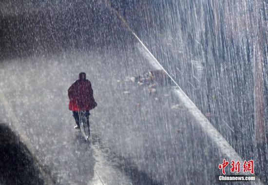 资料图:市民在暴雨中骑行。 中新社发 胡国林 摄