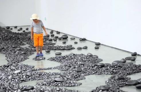 艺术家孟柏伸的作品《河》的展览现场布满了用铅笔涂抹过的石子,观众可以任意穿梭,感受其中的魅力。
