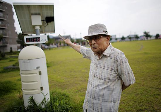 当地时间2015年7月30日,日本福岛,87岁的Atsushi Hoshino在他家附近的一个公园内,旁边是一个辐射监测仪。视觉中国 资料
