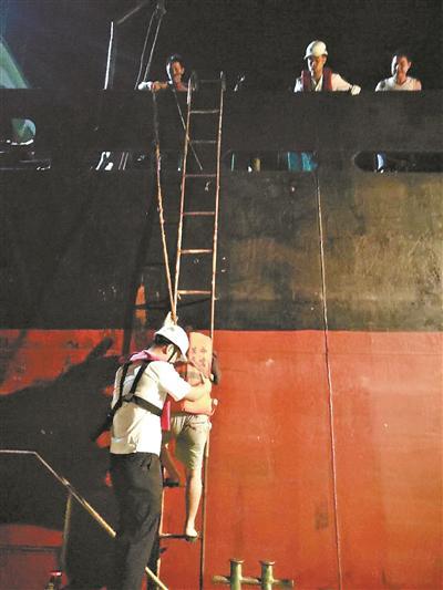 海事执法人员铺设软梯保护陈小姐过渡到海事趸船。