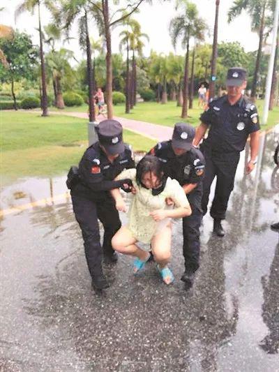 两名女保安员将女子抬出湿滑的路面。