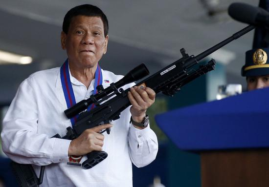 杜特尔特4月拿着警政署长呈给他看的步枪(图:美联)