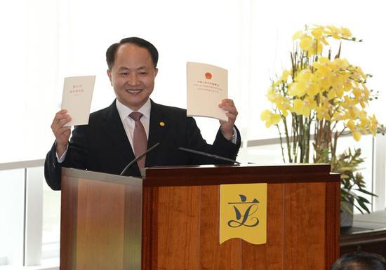 """王志民在""""世界读书日""""这天向立法会议员赠送两本书,分别为《宪法和基本法》合订本和《邓小平论香港问题》(图:香港中联办)"""