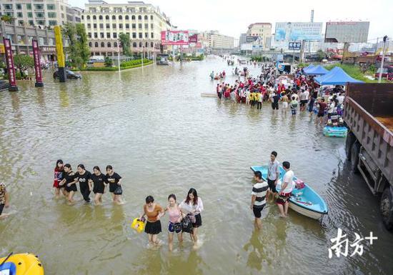 省道237上,大雨带来的积水导致交通堵塞,由于积水深,一些女士手挽手趟过积水。