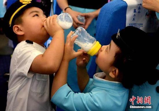 资料图:两名儿童在喝牛奶。 王东明 摄