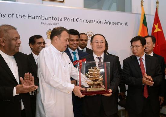在汉班托塔港运营协议签署仪式上,斯里兰卡港口运输部部长马欣达·萨马拉辛哈和中国招商局港口控股有限公司副主席胡建华交换礼物。