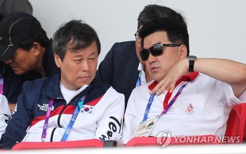 當地時間8月22日,在印尼雅加達,韓國文化體育觀光部長官都鍾煥(左)與朝鮮體育相金一國一同觀看2018雅加達亞運會賽艇項目韓朝聯隊的比賽。圖片來源:韓聯社。
