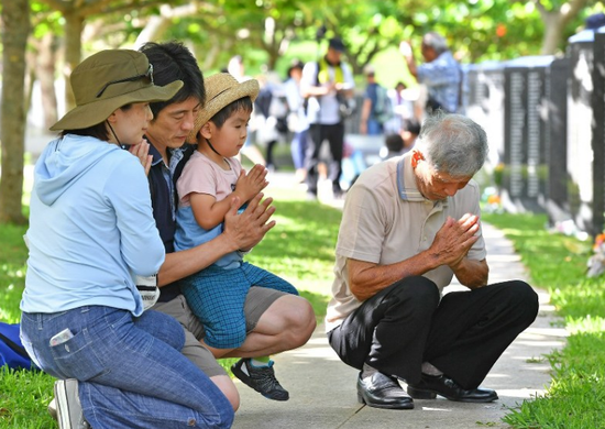 人们在纪念碑前祈祷(每日新闻)