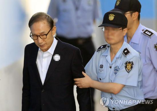 15日,李明博在狱警搀扶下行走