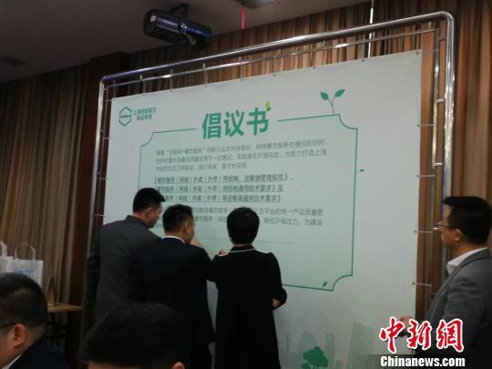 商户代表在倡议书上签字,承诺执行团体标准。 许婧 摄