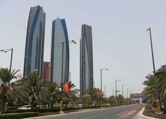 7月18日,阿联酋首都阿布扎比的街道两边悬挂着中阿两国国旗。(邬惠我 摄)