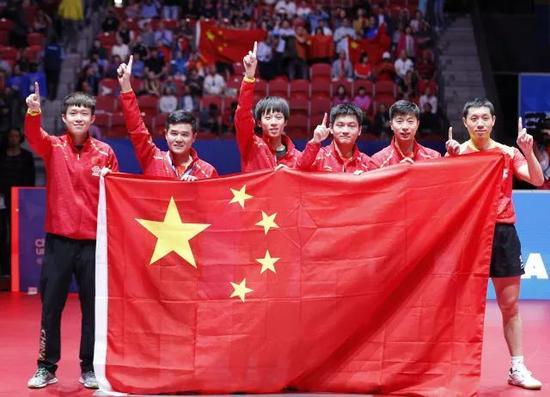 图为中国队队员和教练刘国正(左二)夺冠后手持国旗庆祝。