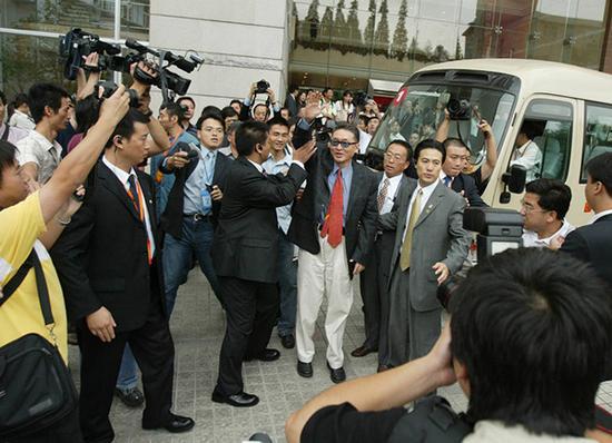 """2005年9月26日,上海复旦大学,两名青年学子在校园里穿上""""敖之迷""""的T恤衫等待李敖的出现。当天,台湾知名学者、作家李敖在这里发表演讲,在校园里引发了一场狂追李敖的热潮。澎湃新闻 资料图"""