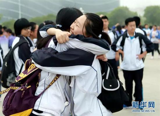 6月8日,在山东省青岛西海岸新区实验高级中学考点,两名考生在考试结束后拥抱在一起。 当日,全国部分地区2018年高考结束。新华社发(王培珂 摄)