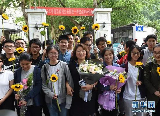 6月9日,在南京金陵中学考点门前,考生在考试结束后与送考老师(中)合影。
