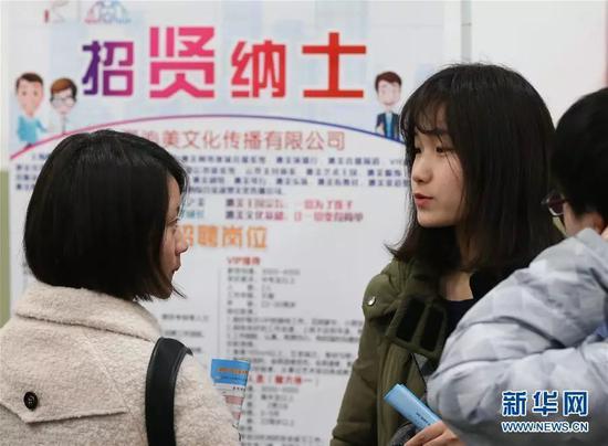 资料图:毕业生在招聘会现场交流。新华社记者 丁汀 摄