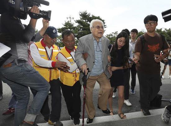 当地时间2018年8月19日,韩国江原道束草市韩华度假村,参加韩朝离散家属团聚活动的一名101岁韩方老人在红十字会工作人员搀扶下抵达当地。 东方IC 图