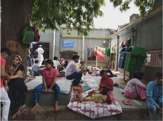 在新德裡一傢公立醫院外面,人們等待接受治療。(美國《華盛頓郵報》網站)