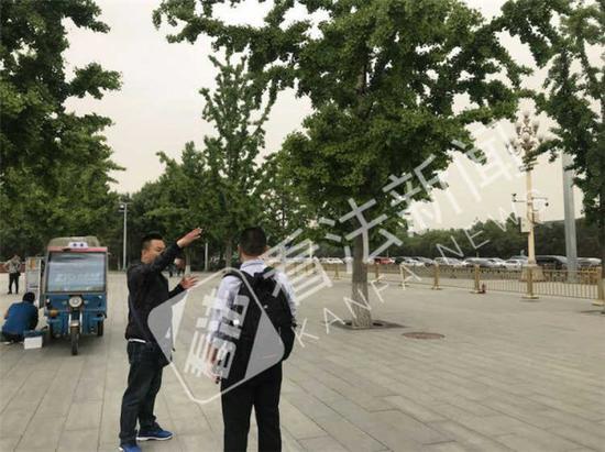 """男子在向记者推荐""""皇城外八景""""游览 摄/记者 董振杰"""
