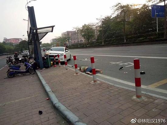一辆白色小轿车的前身撞上公路边上的公交车站,一旁有人躺在路面上,疑似受伤。
