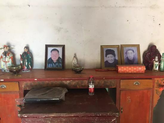 周继坤在大周庄的家里,父亲的遗像摆在客厅的木桌上。新京报记者赵蕾摄