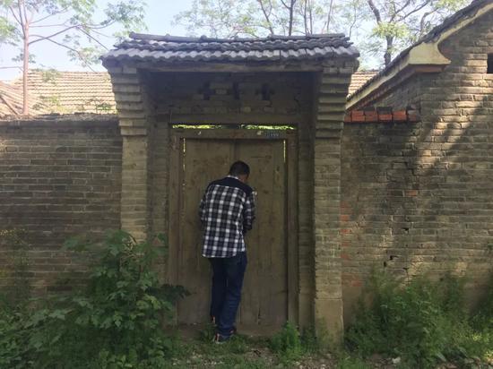 4月19日,周家华回到废弃的老房子,他正在开锁。新京报记者赵蕾摄