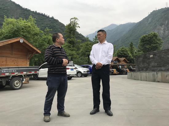 张通荣(右)与当地居民交谈/受访者供图