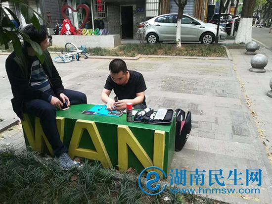 工程师在街边石板凳为顾客修理手机。