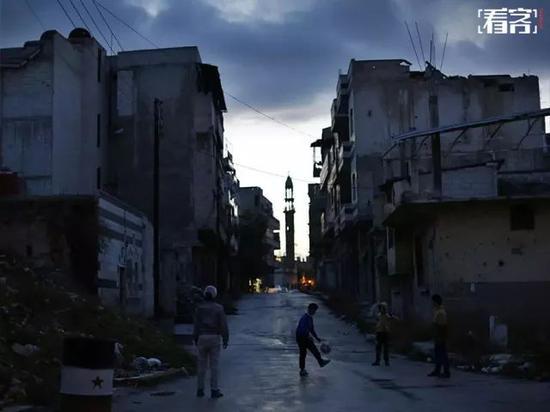 叙利亚阿勒颇,孩子们在一片废墟前踢足球。